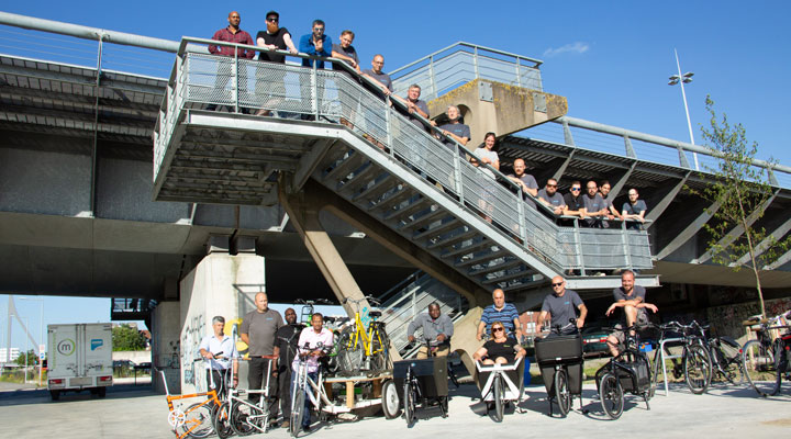 People standing on a staircase and sitting on different types of bicycles.