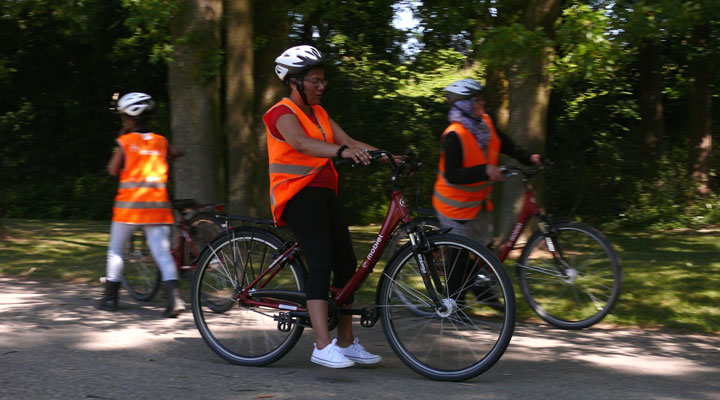 Three people wearing cycling helmets and visibility vests are training to ride a bicycle.