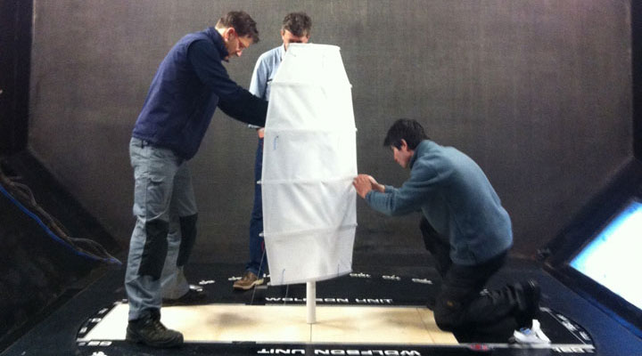 Two members of the SAIL team fixing a new type of modern sail for trial.