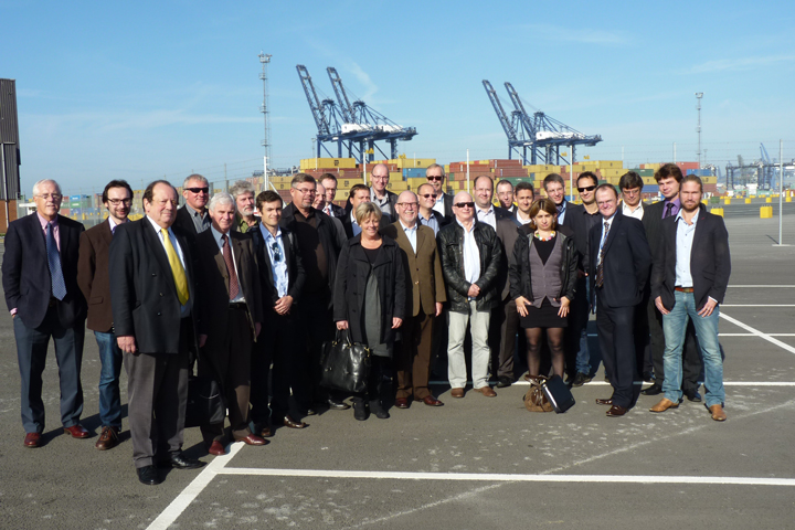 The DRYPORT project team gathered at Felixstowe Port with blue sky, containers and cranes in the background.