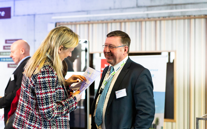 Two people discuss  at a healthcare  event